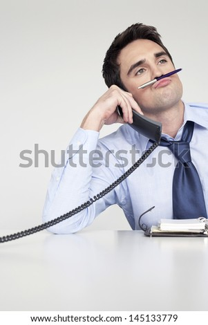 Young businessman using telephone while holding pen as a mustache above lips at desk in office
