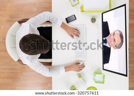Young Businessman Videochatting With Senior Staff On Computer In Office - stock photo