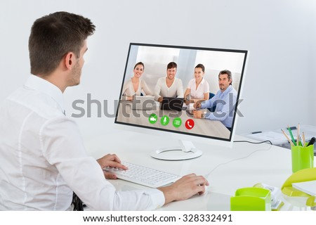 Young Businessman Videoconferencing With Colleagues On Computer