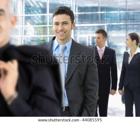 Young businessman walking among others in office lobby, smiling. - stock photo