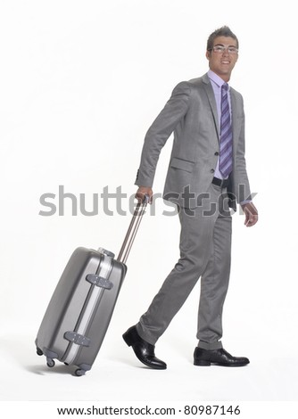 Young businessman walking and pulling his luggage. - stock photo
