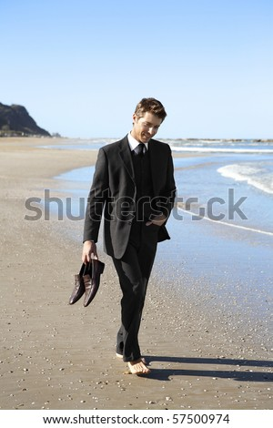 Young businessman walking barefoot on beach - stock photo