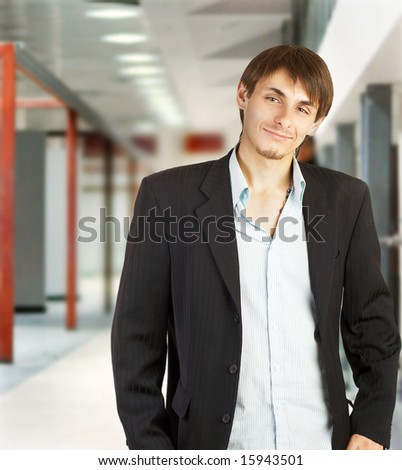 Young businessman walking in a corridor of a modern office building - stock photo