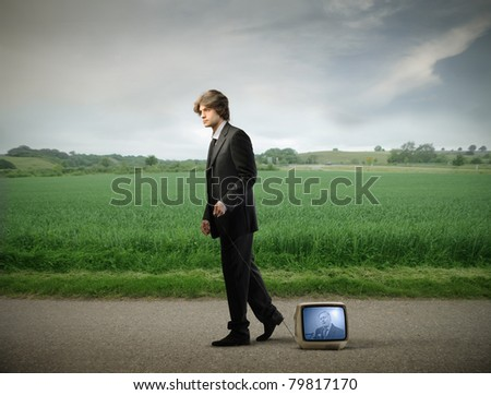 Young businessman walking on a countryside road and carrying a television - stock photo
