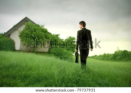 Young businessman walking on a meadow towards an old house - stock photo