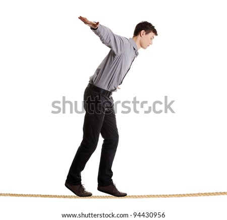 Young businessman walking on rope. Risk in business concept.  Studio shot, isolated on white background.