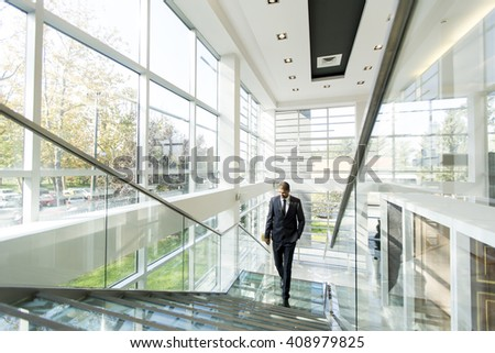 Young businessman walking up the stairs in the office building - stock photo