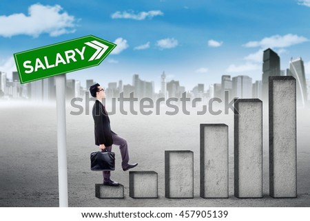 Young businessman walking upwards on the graph with salary text on the signpost