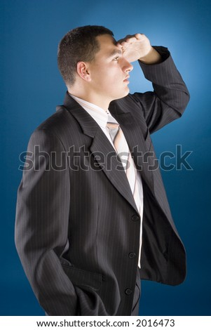 young businessman watching - hand at his forehead (blue background) - stock photo