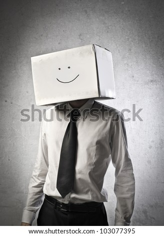 Young businessman wearing a carton with a smiley face on it - stock photo