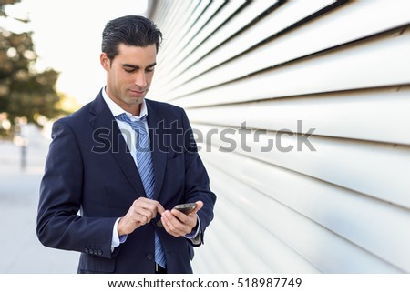 Young businessman wearing blue suit and tie using a smartphone in urban background. Man with formal clothes in the street.