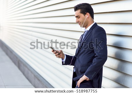 Young businessman wearing blue suit and tie using a smartphone in urban background. Man with formal clothes and headphones in the street.