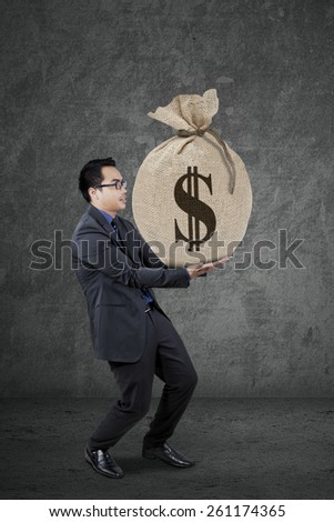 Young businessman wearing formal suit and carry a money sack