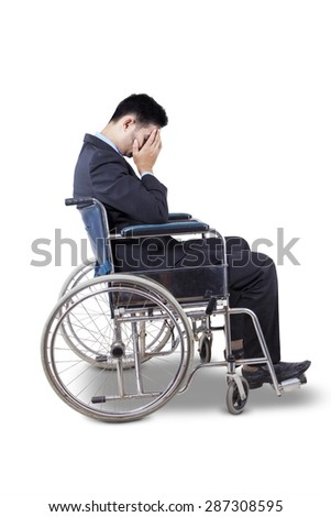 Young businessman wearing formal suit and looks sad, sitting in the wheelchair, isolated on white - stock photo