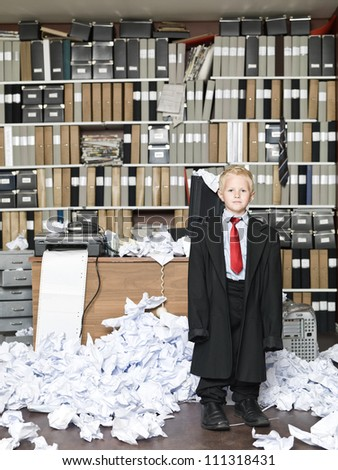 Young Businessman wearing oversized clothes in messy office - stock photo