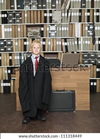 Young Businessman wearing oversized clothes in the office - stock photo