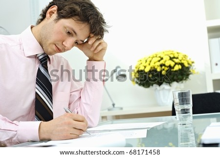 Young businessman wearing pink shirt, sitting at office desk and writing on paper, leaning on hand, thinking. - stock photo