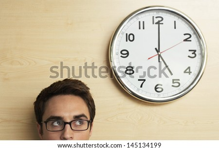 Young businessman wearing spectacles looking at clock on wooden wall in office - stock photo