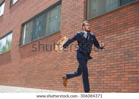 Young businessman with a briefcase and glasses running in a city street on a background of red brick wall - stock photo