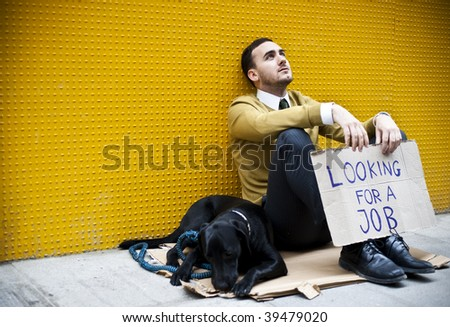 Young businessman with a dog holding sign Looking for a job - stock photo