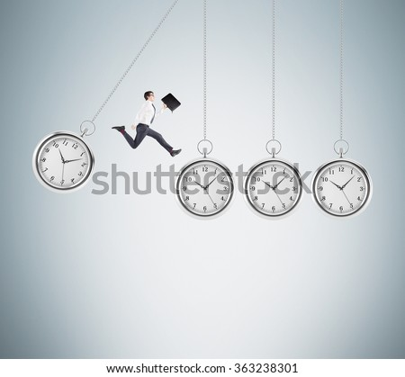 Young businessman with a folder in hand jumping from one hovering pocket watch to another, light grey background. Concept of coping with the task.