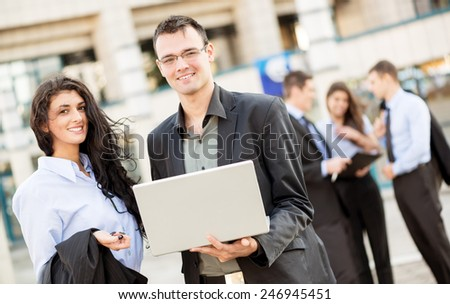 Young businessman with a laptop and businesswoman standing in front of office building separated from the rest of the business team. With a smile looking at the camera. - stock photo