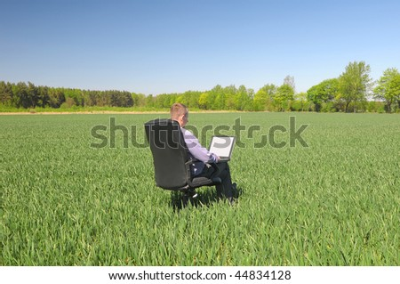 Young businessman with a laptop on the chair in the green field. - stock photo