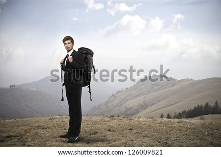Young businessman with a travel backpack standing on a hill - stock photo