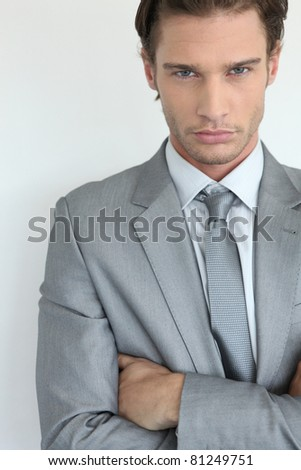Young businessman with arms crossed - stock photo