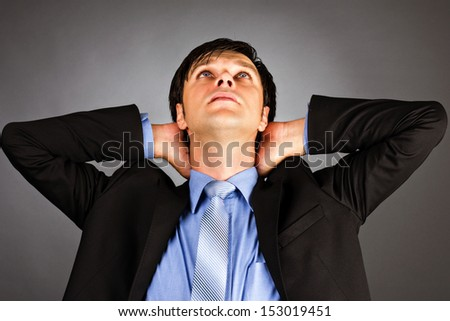 Young businessman with arms crossed behind head against gray background - stock photo