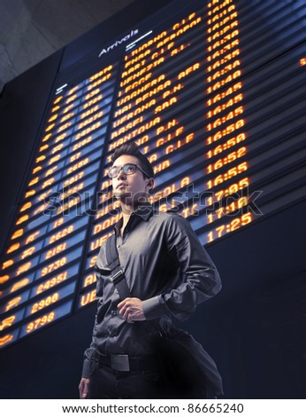 Young businessman with arrivals board in the background - stock photo