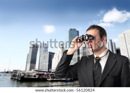 Young businessman with binoculars with cityscape on the background - stock photo
