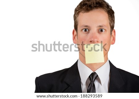 Young businessman with blank note on his mouth, isolated on white background. - stock photo