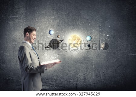 Young businessman with book and planets of space spinning around - stock photo