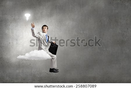 Young businessman with briefcase sitting on cloud