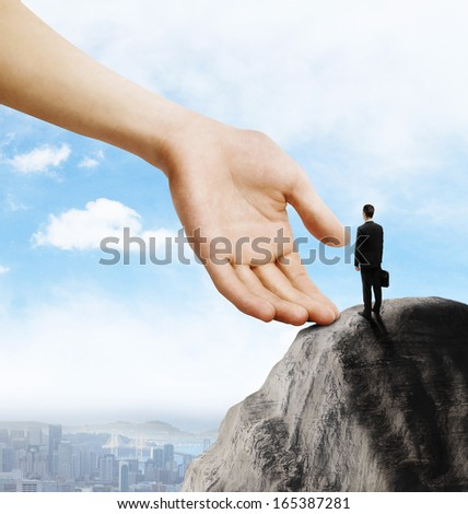 young businessman with briefcase standing on mountain - stock photo