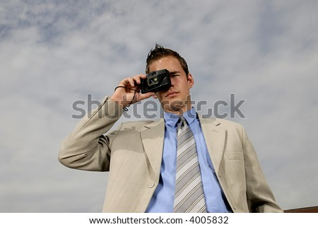 Young businessman with camera in his hands taking picture