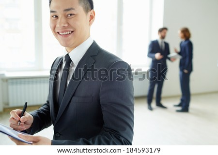 Young businessman with clipboard writing plan and looking at camera in working environment - stock photo