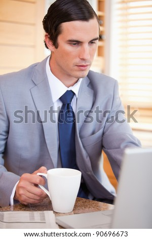 Young businessman with coffee on his laptop - stock photo
