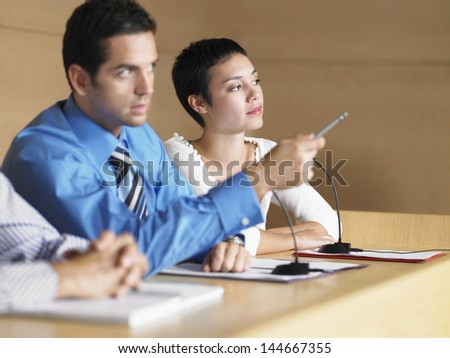 Young businessman with colleagues giving presentation in conference room - stock photo