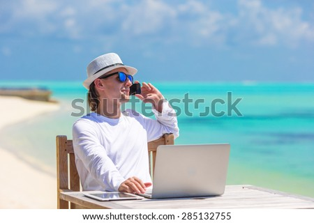 Young businessman with computer and cell phone on white beach - stock photo