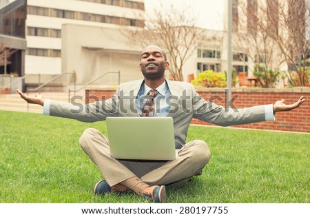 Young businessman with computer relaxing outside corporate office sitting on green grass in mediation mode  - stock photo