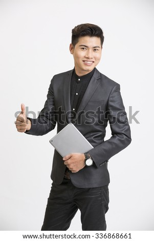 Young businessman with digital tablet and showing thumbs up on white - stock photo