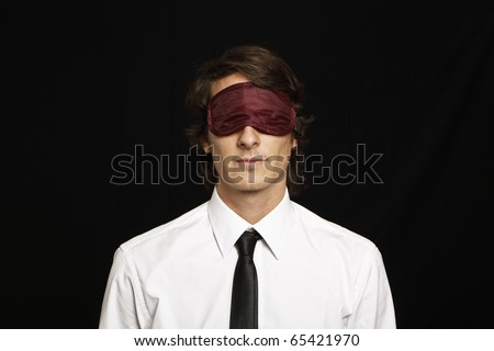 young businessman with eyes covered by sleep mask - stock photo