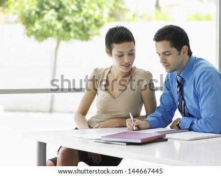 Young businessman with female colleague going over document information at office desk - stock photo