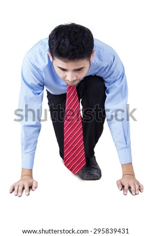Young businessman with formal suit in ready position to race, isolated over white background - stock photo