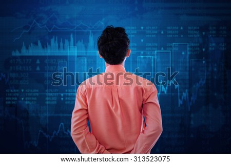 Young businessman with formal suit, looking at stock exchange graph - stock photo