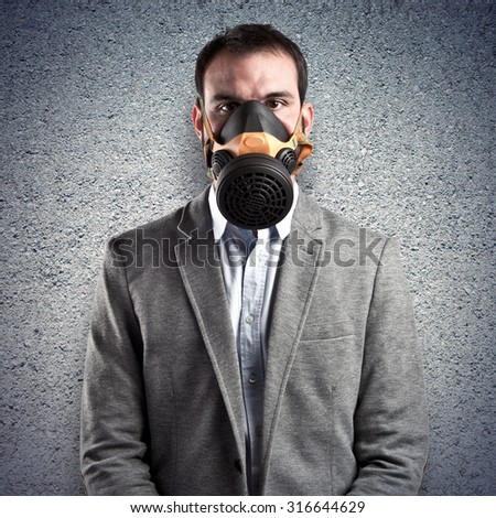 young businessman with gas mask over textured background - stock photo