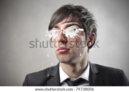 Young businessman with glasses covered with milk - stock photo