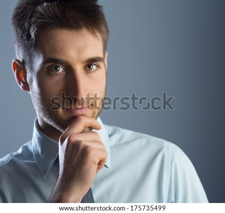 Young businessman with hand on chin, looking at camera. - stock photo